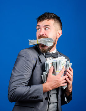 Businessman surprised feels like thief with lot of cash in hands. Steal money. Thief with piles dollars money. Earnings surprise concept. Man bearded businessman hold pile money blue background