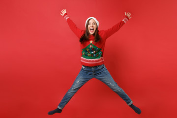 Funny young Santa girl in Christmas hat keeping mouth wide open, jumping spreading hands and legs isolated on red background. Happy New Year 2019 celebration holiday party concept. Mock up copy space.