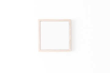 Wooden square frame mockup on white wall. Poster mockup. Clean, modern, minimal frame. Empty fra.me Indoor interior, show text or product