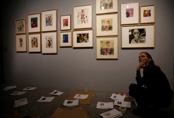 "An employee works on installation of paintings during a preview of the exhibition ""Chagall, From black and white to colour"" at the Caumont Centre d'Art in Aix en Provence"