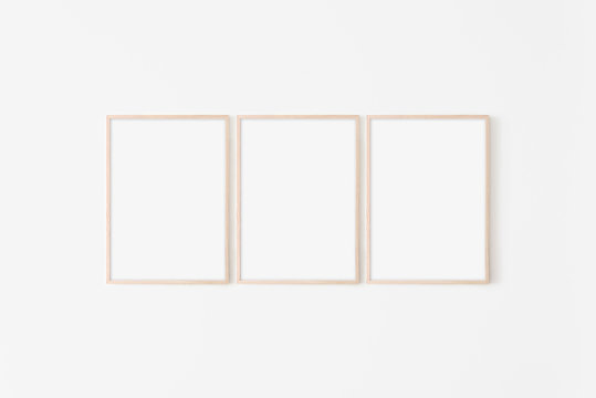 Set of three large 50x70, 20x28, a3,a4, Wooden frame mockup on white wall. Poster mockup. Clean, modern, minimal frame. Empty fra.me Indoor interior, show text or product