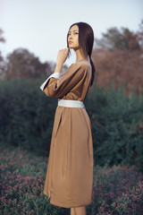 Asian woman wearing traditional japanese kimono outdoors in park. Stylish japanese model posing outdoors in fashionable dress. Young sensual girl standing on flower field