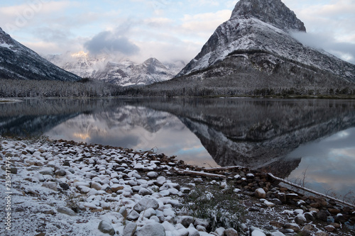 mt grinnell reflected in swiftcurrent lake in the early dawn light