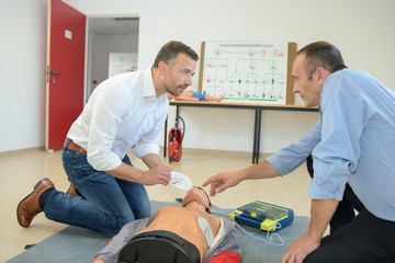 Men doing first aid with dummy