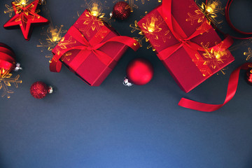 Christmas and New Year holiday background. Xmas greeting card. Red Christmas gifts on blue background top view.