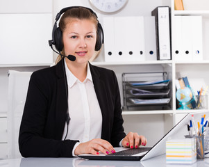 Young dispatcher in black suit is talking by headset with client