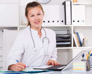 Therapist female in uniform is working behind laptop with documents