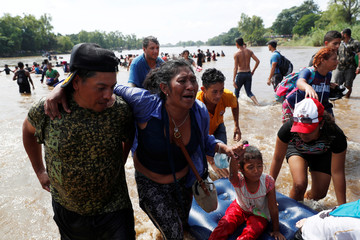 Honduran migrant Celenia Vazquez is being helped by family members and fellow migrants after crossing the Suchiate river, the natural border between Guatemala and Mexico, as she and others try to reach the U.S., in Ciudad Hidalgo