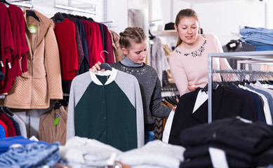 Glad teen girl looking for clothing with mum