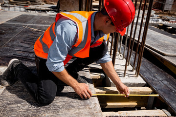 Man dressed in shirt, orange work vest and helmet measures the hole with a tape measure on the building site