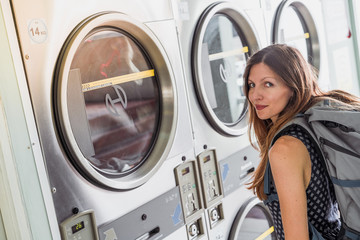 Young backpacker stopping in a laundry since she is doing an Interrail
