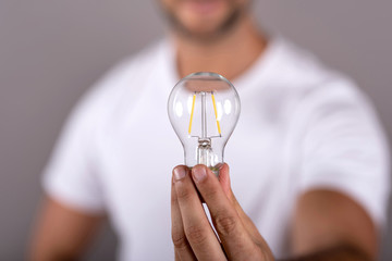 Closeup photo of a lightbulb while a man holding it in a white tshirt in front of a grey background in the studio.