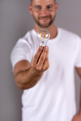 A smiling young man in a white tshirt holding a lightbulb and standing in front of a grey background in the studio.