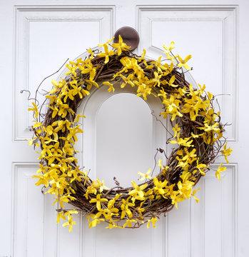 Yellow forsythia wreath on white front door.