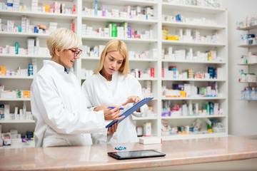 Mature and young female pharmacists working together, standing behind the counter and going over a checklist on a clipboard. Medicine and healthcare concept