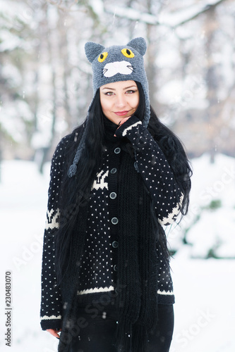 2387d2ad110 Beautiful young woman in winter outfit and cat knitted hat outdoors in park  on snowy day. Natural lighting