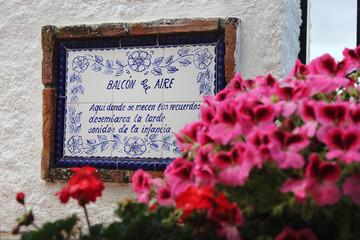 Poema escrito en azulejo en la pared, adornado con macetas con flores de color rosa y rojo.