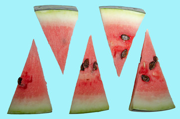 Watermelon slices cut into triangles, watermelon bones. Blue background.