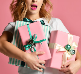 Beautiful woman composition hold pink and pastel green Christmas presents gifts for new year celebration