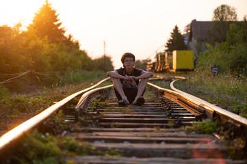 The boy walks on the rails