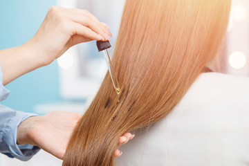 Close-up drop of oil restore and recovery hair is applied to head bulbs. hairdresser spa salon.