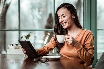 Relaxed atmosphere. Charming brunette keeping smile on her face while staring at screen of her tablet