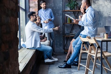 Full length of young modern people in smart casual wear having a meeting in the creative office