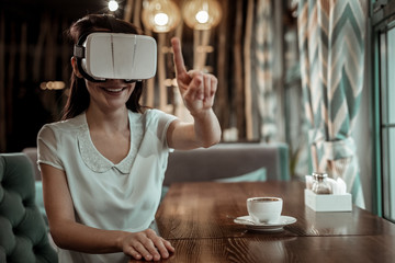 I see it. Positive delighted girl raising her forefinger while testing mask for virtual vision