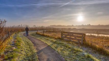 Keuken foto achterwand Ochtendgloren Walking track in misty polder landscape