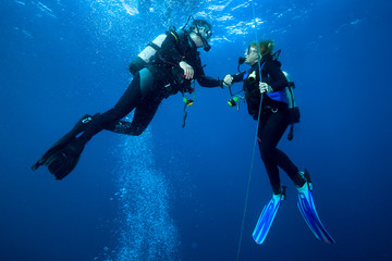 Spoed Fotobehang Duiken Happy couple scuba divers hovering together on a safety stop