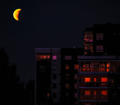 A lunar eclipse above an apartment building