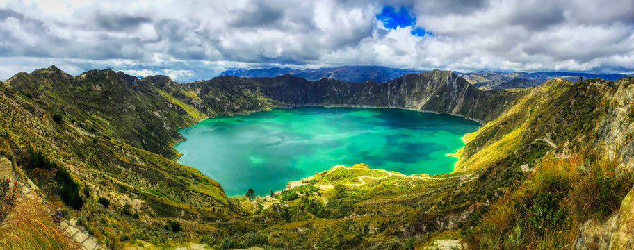 A bird's eye panoramic view of the bright green volcanic Quilotoa Lake in Ecuador with lots of white and grey clouds in a blue sky and green brush on the side of the caldera