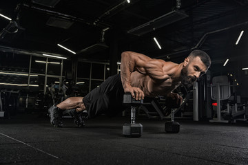 Young handsome male athlete bodybuilder weightlifter with idial abdominals, doing exercises in modern gym on a dark background. Exercises for biceps.