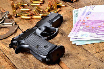 9mm pistol gun, bullets, handcuffs and euro banknotes on old wooden table