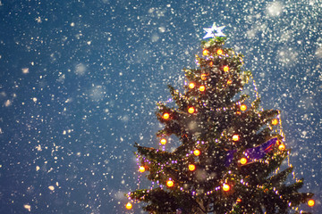 Illuminated christmas tree at night with falling snow and copy space