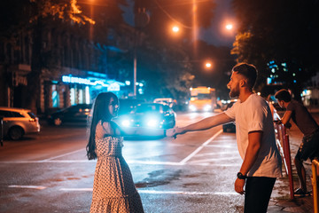 Young couple in the streets of the evening city