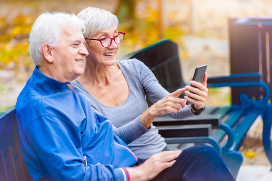 Smiling senior active couple sitting on the bench looking at smartphone