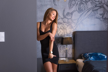 Sensual photo of a beautiful woman in an elegant black dress while standing against a wall in a modern apartments bedroom.
