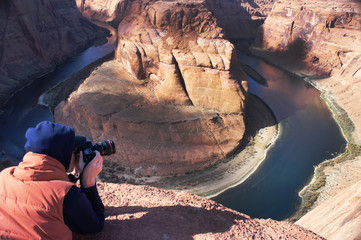 A photographer is taking pictures of Horseshoe Bend in Arizona, USA