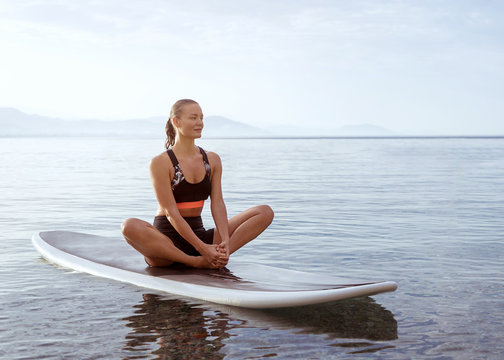 girl sitting on paddleboard on the seaside with montains on background