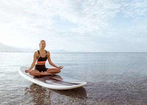 Woman sitting and meditating on paddle board. Yoga pose on sup boarding at the seaside