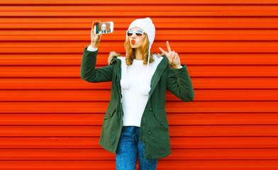 Fashion young woman taking selfie by smartphone on red background