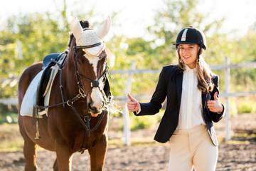 Girl equestrian rider stands near the horse. Horse farm Wall mural