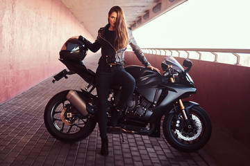 A seductive biker girl leaning on her superbike on a sidewalk inside the bridge on a sunny day.