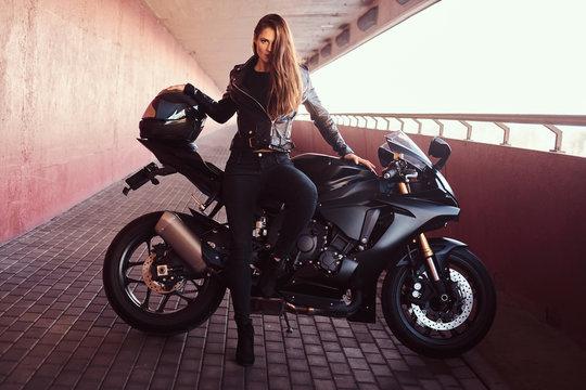 A seductive biker girl leaning on her superbike on a sidewalk inside the bridge on a sunny day.