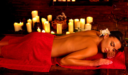 Massage of woman in spa salon. Girl on candles background in massage spa salon. Orchid in her hair. Luxary interior in oriental therapy salon. Spot light on dark background.