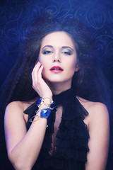 brunette woman with high hair and bright make up, gothic style on a black background