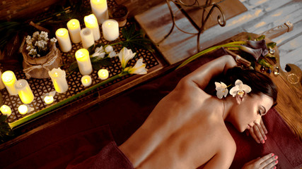 Massage ayurveda of woman in spa salon. Girl to the waist on candles background in therapy room....