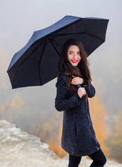 A wonderful girl with an umbrella in her hands stands in the rain