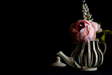 flowers in an unusual teapot on a black background